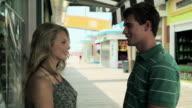 Teenage couple talking on pier