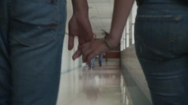 CU TS Teenage couple (16-17) walking along school corridor holding hands, Cazenovia, New York, USA