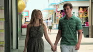 Teenage couple walking hand in hand on pier