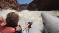 WS POV Teenage girl (16-17) and boy (10-11) rafting on Colorado river in Grand Canyon with water splashing on them / Grand Canyon Village, Arizona, USA