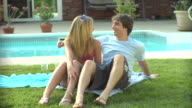MS, Teenage girl and boy (16-17) relaxing beside pool, Middlesex, New Jersey, USA