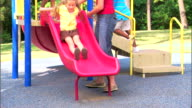 Teenage girl and children at a playground