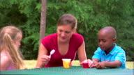 Teenage girl and children with gelatin dessert
