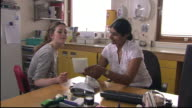 MS, DS, Teenage girl (16-17 years) and doctor talking in office, girl receiving prescription