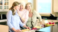 Teenage girl baking with mother and grandmother