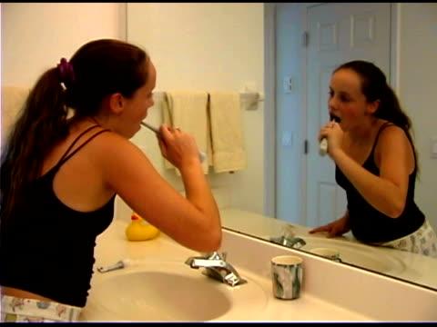 Teenage girl brushing teeth in bathroom