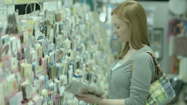 MS, PAN, SELECTIVE FOCUS, Teenage girl (16-17) choosing greeting card in pharmacy aisle, Scotch Plains, New Jersey, USA