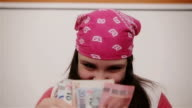 Teenage girl counting it's allowance and smiling