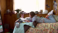 MS ZI teenage girl doing homework on bed with laptop/ turning and smiling at camera
