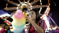 Teenager-Mädchen essen Zuckerwatte im Vergnügungspark