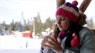 Teenage girl eating sandwich on ski break