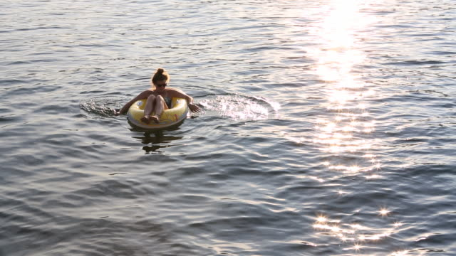 Teenage girl floats on plastic raft across lake from sunset