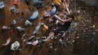 teenage girl free climbing an indoor climbing wall