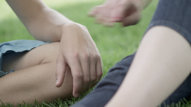 Teenage girl holds boy's hand while sitting on the grass.