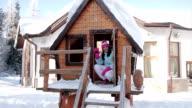 Teenage girl in wooden chalet,winter scene
