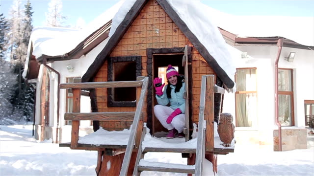 Teenage girl in wooden chalet,winter scene