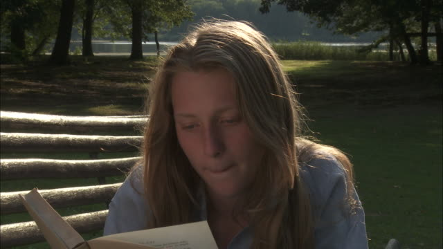 CU Teenage girl (14-15) lying on bench and reading book, Bouillon, Belgium