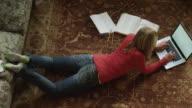 WS HA Teenage girl (14-15) lying on carpet and using laptop / Cedar Hills, Utah, USA