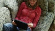 MS TU HA Teenage girl (14-15) lying on sofa and using digital tablet / Cedar Hills, Utah, USA