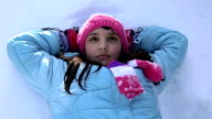 Teenage girl Lying on the snow and resting