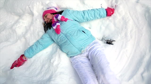 Teenage girl makes a snow angel