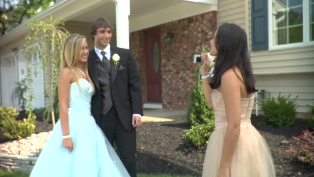 MS, Teenage girl (16-17) photographing couple in prom attire in front of house, Edison, New Jersey, USA