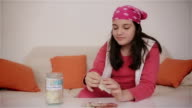 Teenage girl putting money into savings jar