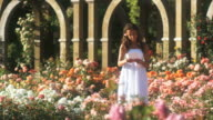 SLO MO WS PAN Teenage girl (16-17) reading letter in summer garden, Lehi, Utah, USA