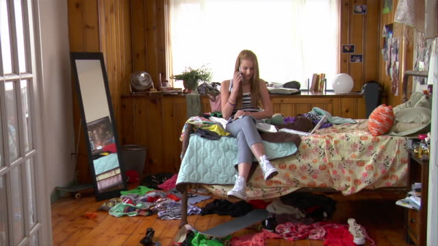 WS teenage girl reading on bed/ girl answering mobile phone