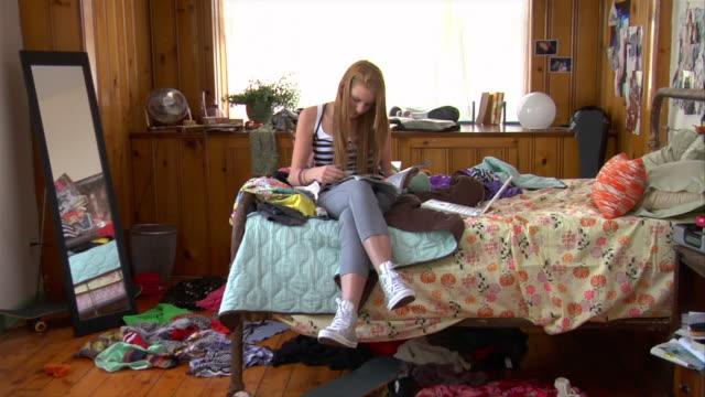 MS ZO teenage girl reading on bed/ ZI girl answering mobile phone