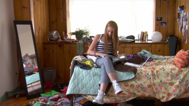 WS ZI teenage girl reading on bed/ ZO girl reading