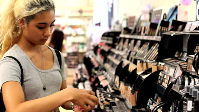 Teenage girl shopping for makeup. Shakes nail polish.