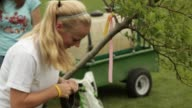 Teenage girl shoveling sod in order to plant a tree