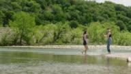 Teenage girl wades into river and kicks water up at sister on shore.