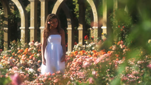 SLO MO WS Teenage girl (16-17) walking through summer garden, Lehi, Utah, USA