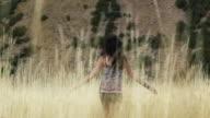 MS Teenage girl (16-17) walking through tall grass in field / South Fork, Utah, USA