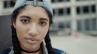 CU SLO MO. Teenage girl with skateboard turns and looks at camera in urban skatepark.