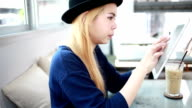 Teenage girl working with tablet in coffee shop cafe.