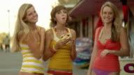 MS Teenage girls (16-17) and young woman at boardwalk eating hamburger / Jacksonville, Florida, USA