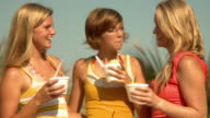 MS Teenage girls (16-17) and young woman eating ice cream on beach / Jacksonville, Florida, USA