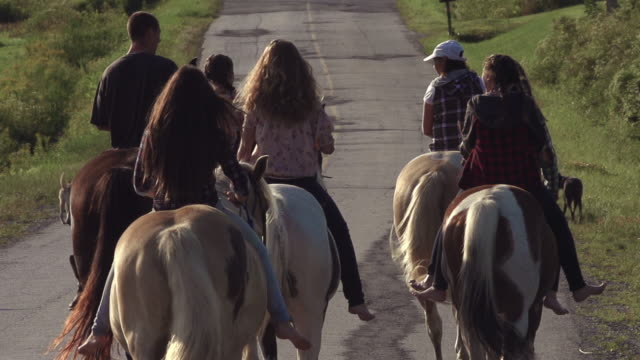 Teenage Girls Group Riding Horses on Country Dirt Road Super Slow Motion