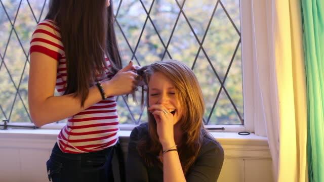 Teenage girls plaiting hair