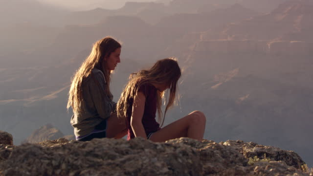 Teenage girls sitting on the edge of a cliff and tossing a rock