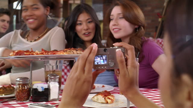 Teenage girls taking pictures with digital camera at pizza restaurant / inviting teenage boys over from next table