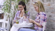 Teenage girls using smart phones in cafe