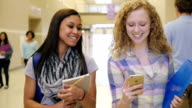 Teenage high school girls laughing and using smart phone in busy hallway