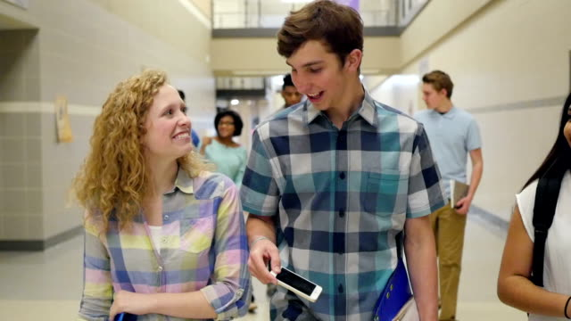 Teenage high school students smiling while walking together in busy hallway