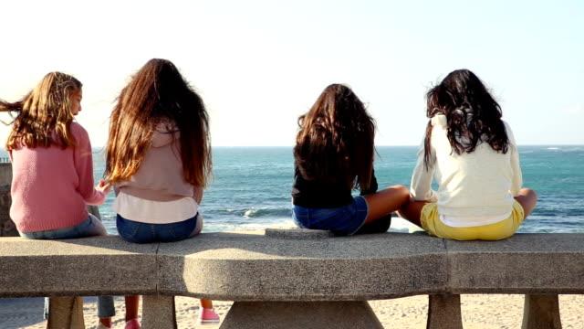 Teenage sisters and friends hanging out together in front of the sea.