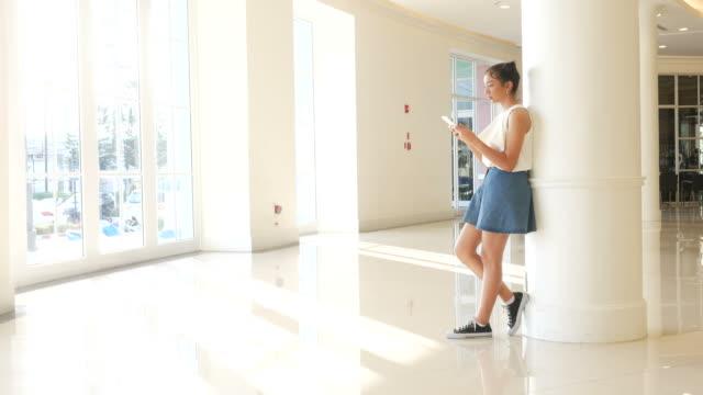teenage woman using smart phone in university