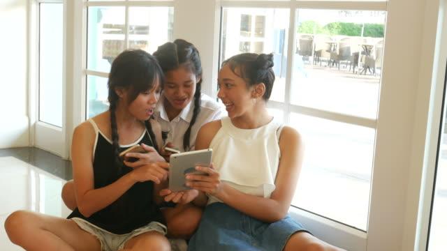 teenage women using smart phone in university
